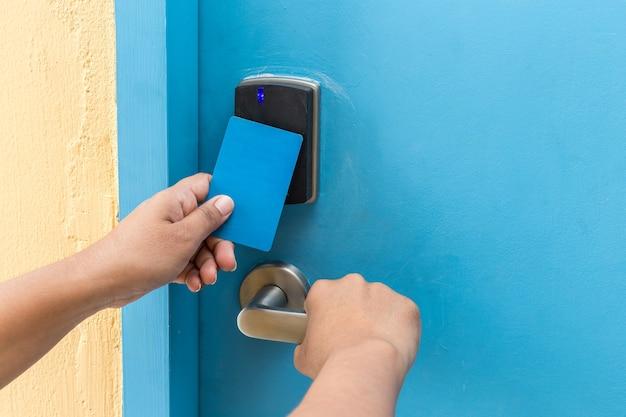 Gros plan main tenant la carte-clé de l'hôtel bleu devant la porte électrique