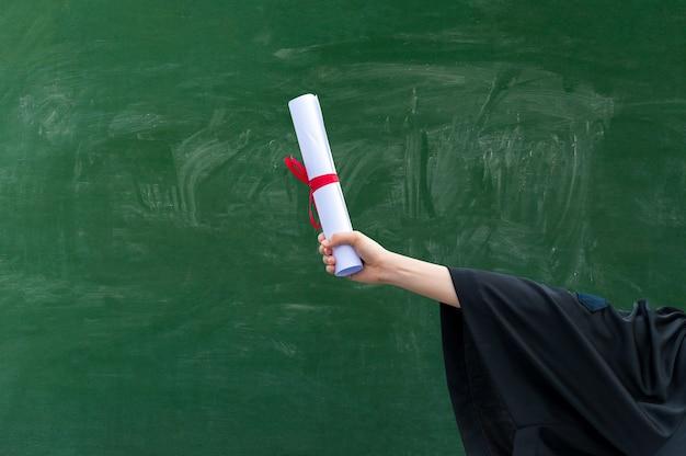 Gros plan sur la main tenant un certificat d'obtention du diplôme