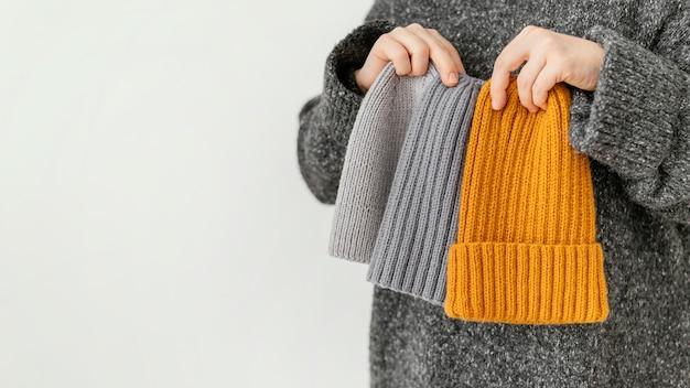 Gros plan main tenant différents chapeaux tricotés