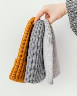 Gros plan main tenant différents chapeaux