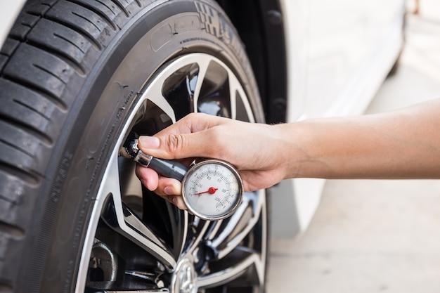 Gros plan de main tenant le manomètre pour la mesure de pression des pneus de voiture