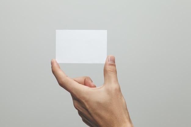 Gros plan d'une main tenant un papier vierge