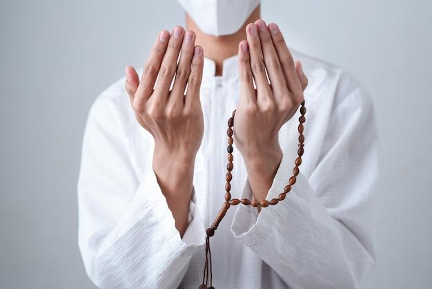 Gros plan main tenant un perles musulmanes ou tasbih avec sur gris
