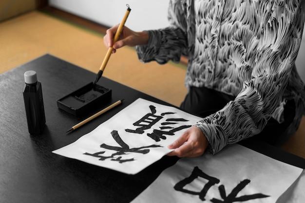 Gros plan main tenant pinceau et papier