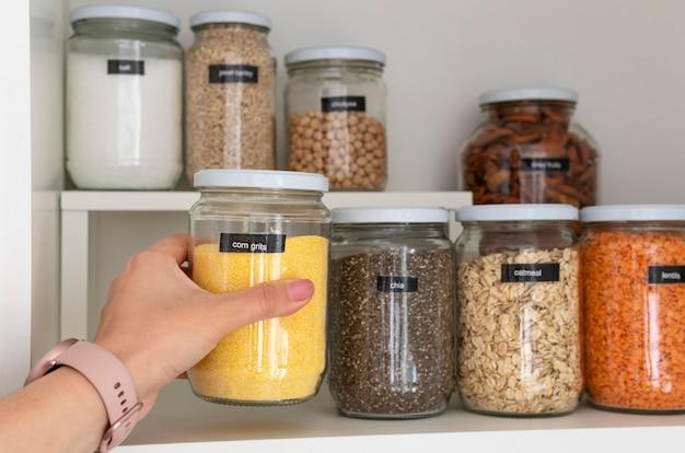 Gros plan main tenant le pot de gruau de maïs
