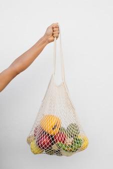 Gros plan main tenant un sac écologique