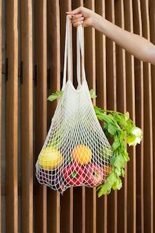 Gros plan main tenant un sac avec des légumes