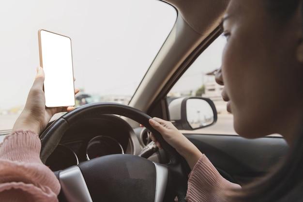 Gros plan de la main tenant le smartphone avec maquette blanche sur fond d'écran du volant de voiture