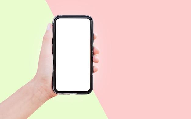 Gros plan de main tenant le smartphone avec une maquette blanche isolée sur deux surfaces de couleurs vertes et rouges.