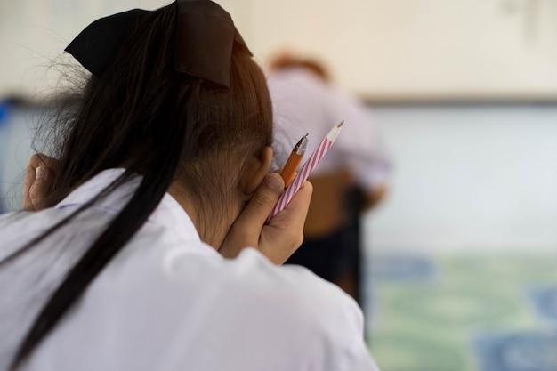 Gros plan d'une main tenant un stylo d'étudiants en uniforme à examiner ou à tester en salle de classe.
