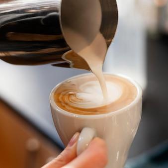 Gros plan main tenant une tasse de café