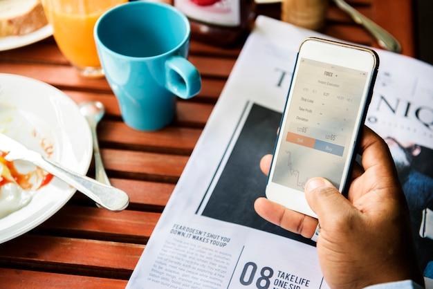 Gros plan d'une main tenant un téléphone portable vérifiant ses stocks en ligne