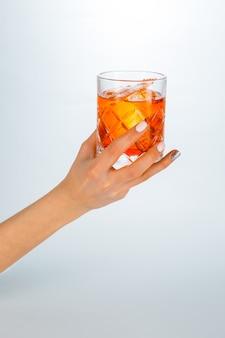 Gros plan d'une main tenant un verre de cocktail negroni sur blanc avec espace de copie.