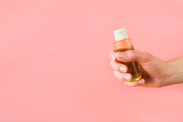 Gros plan, main, tenue, bouteille, huile essentielle, contre, fond coloré