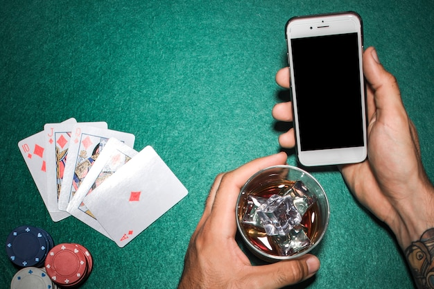 Gros plan, main, tenue, téléphone portable, whisky, verre, table poker