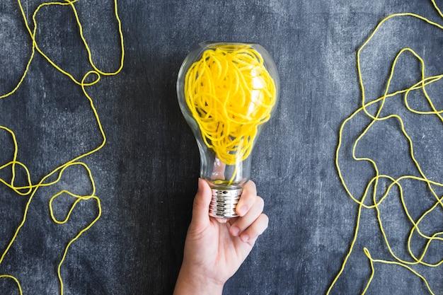 Gros plan, main, tenue, transparent, ampoule, à, jaune, fil, sur, tableau noir