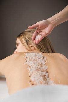 Gros plan d'une main de thérapeute appliquant du sel sur le dos de la femme
