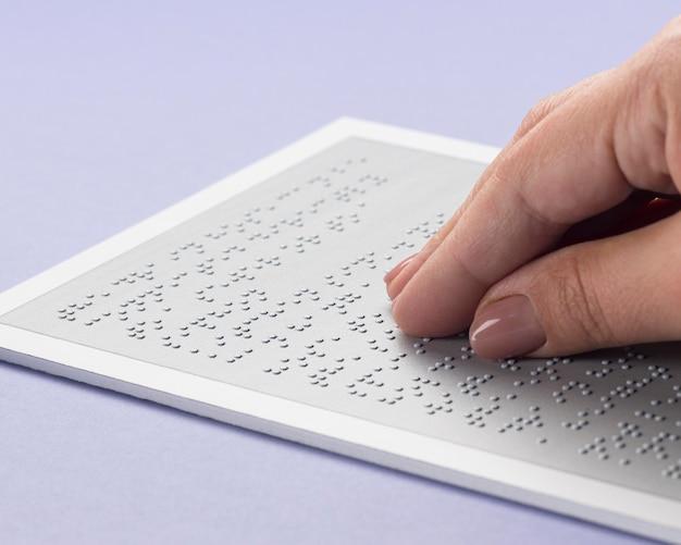Gros plan main touchant l'alphabet braille