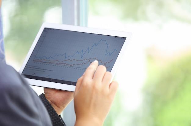 Gros plan sur la main en touchant l'écran de la tablette avec des données graphiques