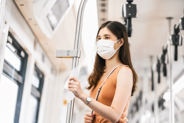 Gros plan sur la main touchant avec une lingette humide d'une jeune passagère asiatique portant un masque chirurgical