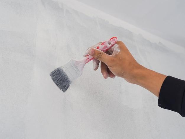 Gros plan de la main de travailleur utilisant le rouleau et le pinceau pour le mur de peinture. concept de construction de maison.