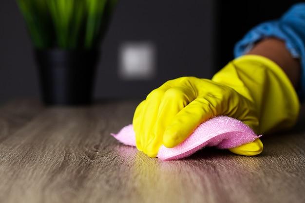Gros plan de la main des travailleurs essuyant la poussière au bureau