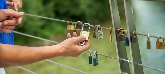 Gros plan de mains accrocher des serrures sur une corde - concept d'amour