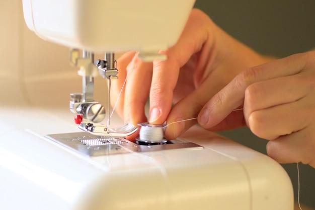 Gros plan des mains à l'aide d'une machine à coudre