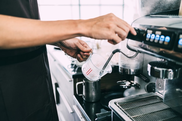 Gros plan des mains de barista fumant sur un bécher à café avec une machine à café.