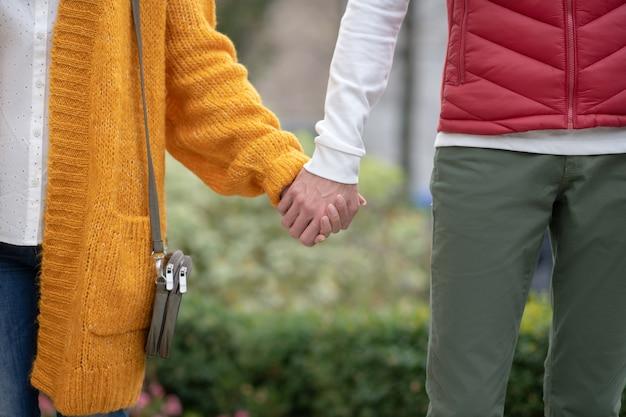 Gros plan des mains de beau jeune couple se tenant ensemble