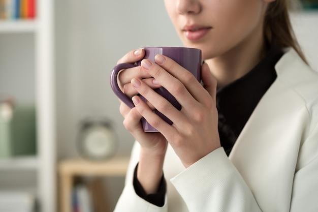 Gros plan des mains de la belle jeune femme tenant une tasse chaude de café ou de thé. café du matin, saison froide, pause-café de bureau ou concept d'amant de café.