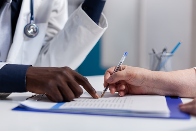 Gros plan des mains sur le bureau à la clinique de soins de santé