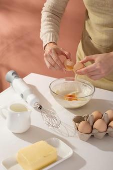 Gros plan sur les mains cassant un œuf
