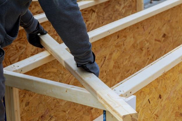 Gros plan des mains d'un charpentier sur un chantier de construction. concentrez-vous sur la perceuse et la main.