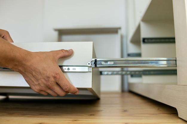 Gros plan des mains de charpentier installant un tiroir en bois sur des patins coulissants dans une armoire contemporaine.