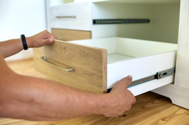Gros plan sur des mains de charpentier installant un tiroir en bois sur des patins coulissants dans une armoire contemporaine.