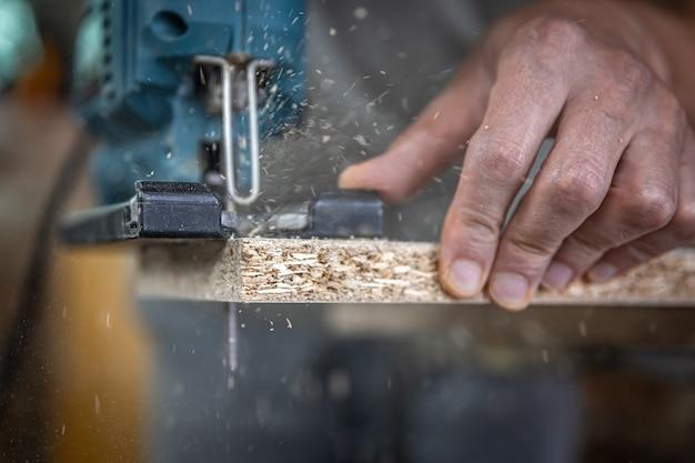 Gros plan sur les mains d'un charpentier en train de couper du bois avec une scie sauteuse.