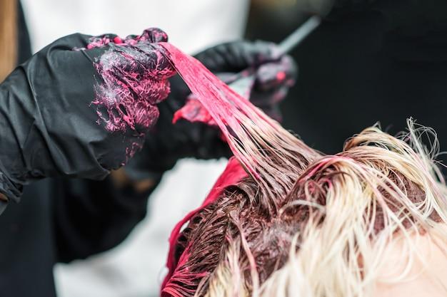 Gros plan des mains d'un coiffeur en gants noirs teignent la mèche de cheveux de la fille du client en rouge.