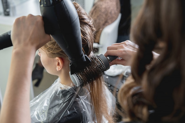 Gros plan des mains des coiffeurs séchant de longs cheveux blonds avec un sèche-cheveux et une brosse ronde