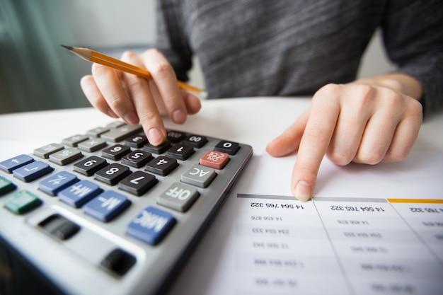 Gros plan des mains comptables comptant sur la calculatrice
