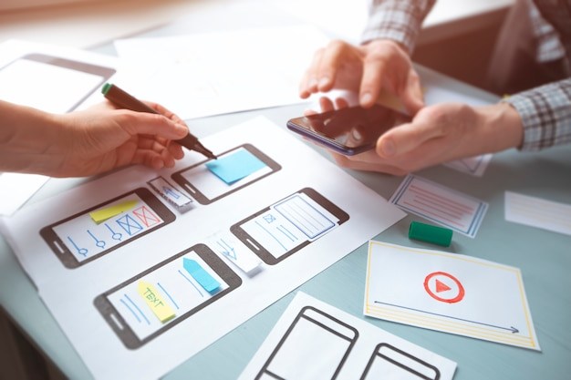 Gros plan sur les mains d'un concepteur web développant des applications pour l'interface utilisateur des téléphones mobiles.