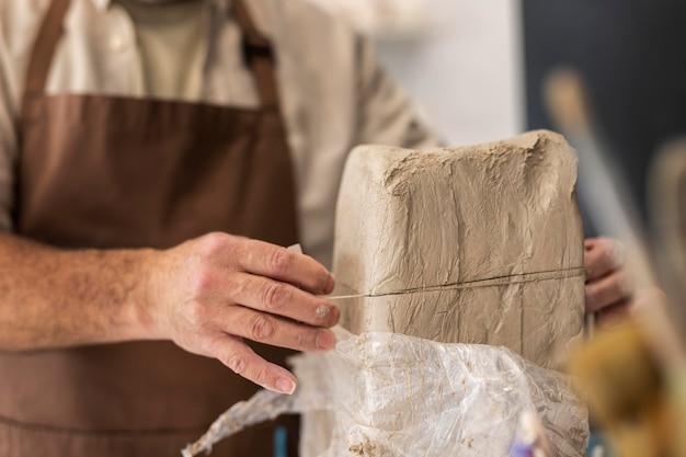 Gros plan des mains coupant l'argile