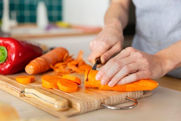 Gros plan des mains coupant la carotte