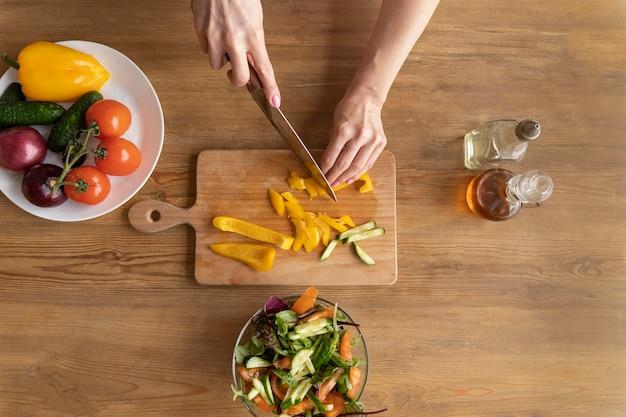 Gros plan des mains coupant des légumes