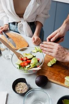 Gros plan sur les mains coupant des légumes