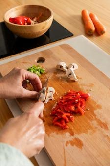 Gros plan des mains coupant le poivre
