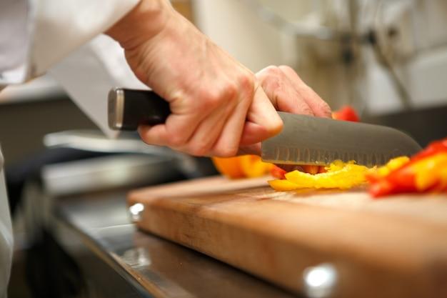 Gros plan sur les mains coupant le poivron jaune