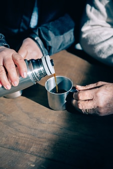 Gros plan des mains d'un couple de personnes âgées versant du café dans une tasse en métal du thermos sur une table en bois