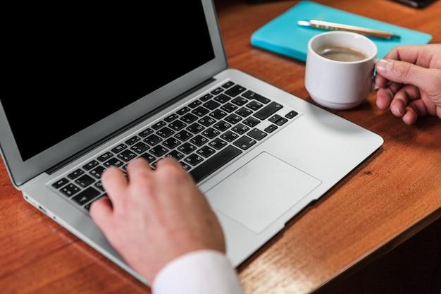 Gros plan, mains, dactylographie, ordinateur portable, café
