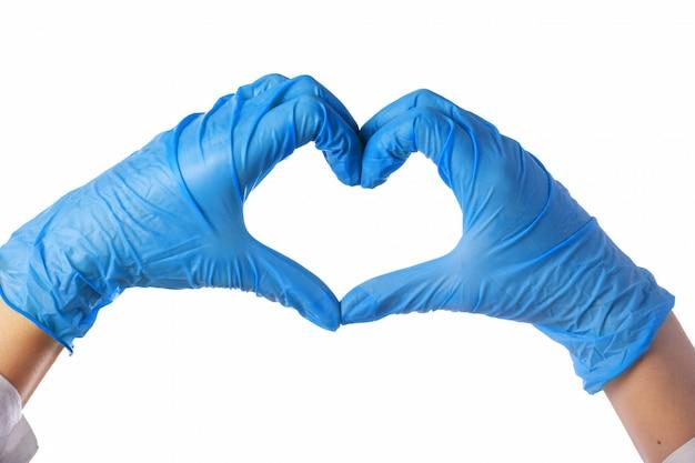 Gros plan des mains dans des gants en latex. le cœur est plié des mains.